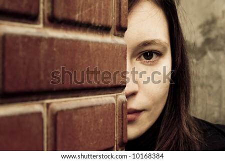 Woman looking behind a brick wall.