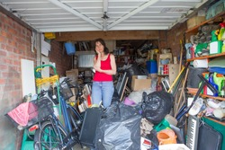 Woman looking bemused about where to start in clearing out her garage