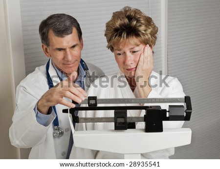Woman looking dismayed at her weight as she is weighed by her doctor on a medical scale.