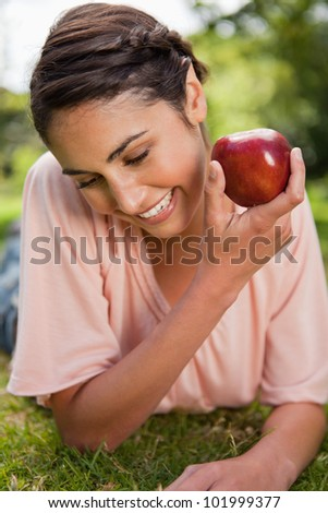 Woman looking down towards the ground while presenting a red apple as she is lying down in grass