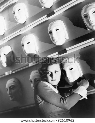 Woman looking frightened holding onto one mask on the wall of masks