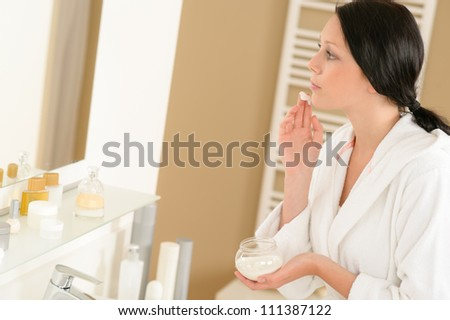 Woman looking in bathroom mirror and applying face moisturizer cream - stock photo
