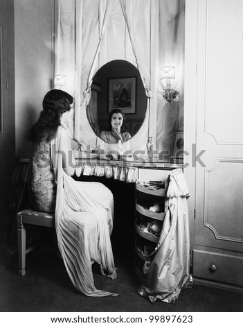 Woman looking in mirror at dressing table