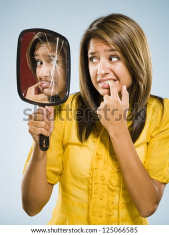 Woman looking into shattered mirror nervously - stock photo
