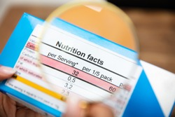 Woman Looking Nutrition Facts On Food Box Through Magnifying Glass