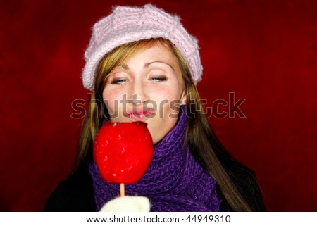 Woman looking on tasty red candy toffee taffy apple on christmas holiday market fair