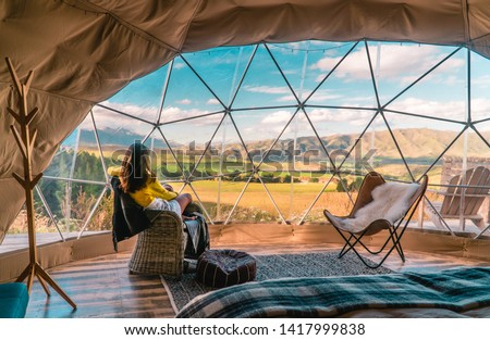 Woman looking out at nature from geo dome tents. Green, blue, orange background. Cozy, camping, glamping, holiday, vacation lifestyle concept. Outdoors cabin, scenic background. New Zealand.