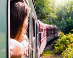 Woman looking out the window of the old train. Bulgarian mountains, Alpine railway in the Balkans
