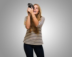 Woman Looking Through A Camera against a grey background