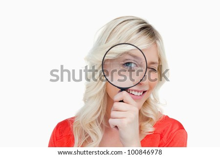 Woman looking through a magnifying glass while showing a blink of an eye - stock photo