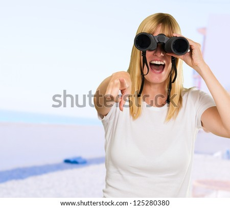woman looking through binoculars and pointing at the beach