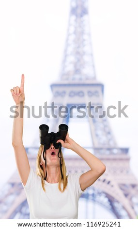 woman looking through binoculars and pointing up in front of the eiffel tower