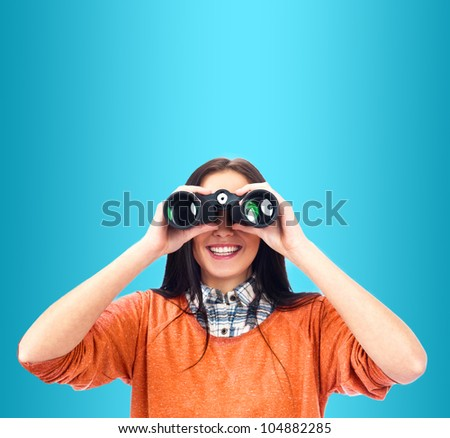 Woman looking through binoculars isolated on blue
