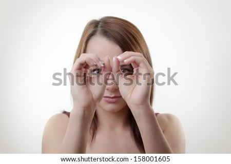 woman looking through binoculars shaped hands
