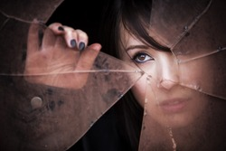 Woman looking through dirty broken glass