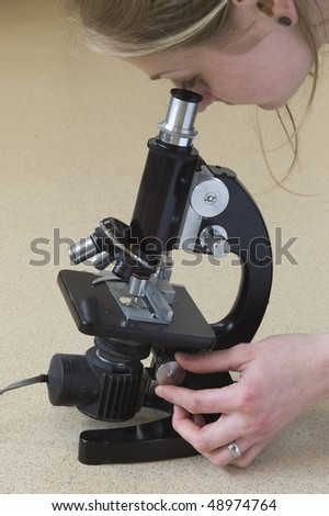 Woman looking through microscope