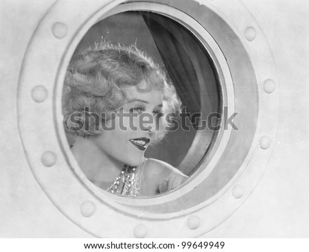 Woman looking through porthole