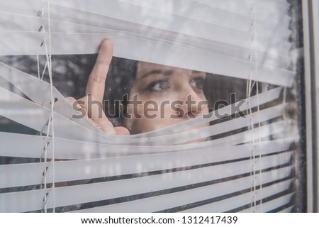 Woman Looking Through the Blinds. Girl looking out the window
