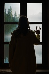 Woman looking through the window at a beautiful spruce forest surrounded by fog. Social distancing as a prevention measure against novel coronavirus 2019-nCoV (Covid-19, SARS-CoV-2) virus infection.
