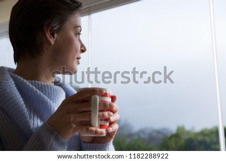 woman looking through window...