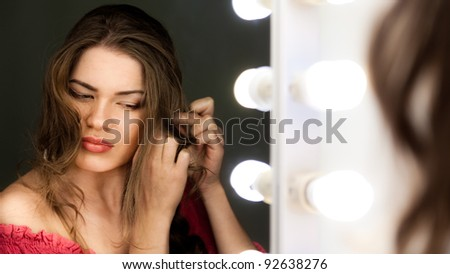 Woman looking to the mirror at studio - stock photo