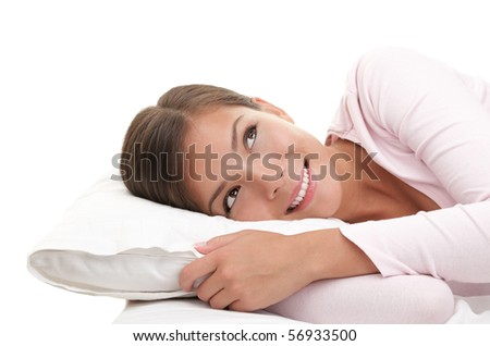 Woman looking up daydreaming. Woman relaxing on bed isolated on white background. - stock photo