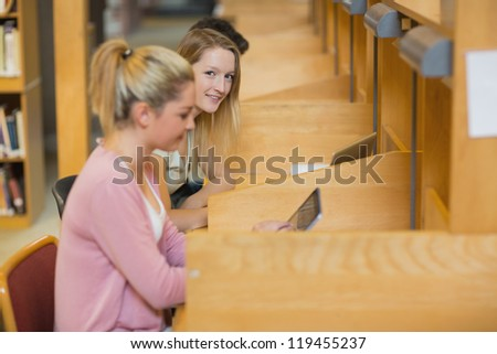 Woman looking up from studying at study desks in college library