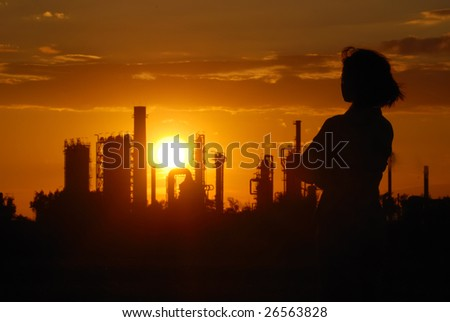 Woman looks on oil refinery at sunset (silhouette)