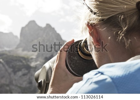 Woman looks through telescope - stock photo