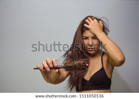 Woman loosing hair holding comb. Young girl losing hair problem, hair lost falling out on brush. Treated healthy medical therapy treatment loosing hair concept.
