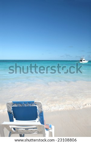 Woman lounging in a chair on a beautiful Caribbean tropical beach with white sand and green ocean, suitable background for a variety of designs