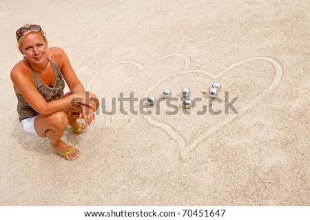 woman loves jeu de boule, posing by balls
