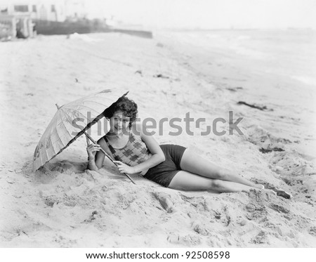 Woman lying at the beach with a sun umbrella