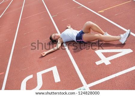 Woman lying down taking break on track field