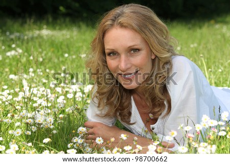 Woman lying in a field of daisies