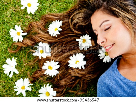 Woman lying in a floral garden with daisies around her head