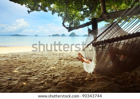 Woman lying in a hammock in tree\'s shadow on a beach