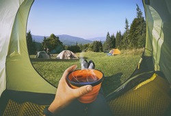 Woman lying in a tent with coffee ,view of camping with  people near the fire   and forest