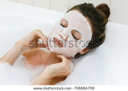 Woman lying in bathtub with a sheet mask on her face #708886798