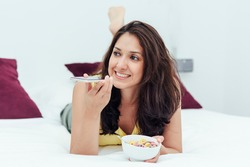 Woman lying in bed with a bowl of cereal while sending a voicemail message. Lifestyles concept.