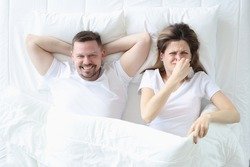 Woman lying in bed with man and covering her nose with her hand