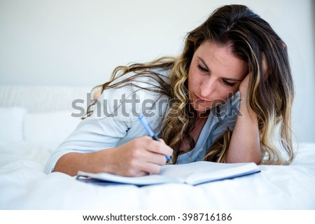 woman lying in her bed, looking sad and writing in a book