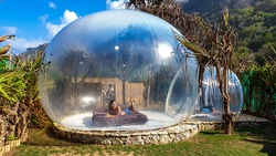 Woman lying on a bed inside of a transparent bubble hotel. The Bubble is located in a small jungle next to Nyang Nyang Beach, Bali, Indonesia. Luxury holiday. The woman is smiling, enjoying the bubble