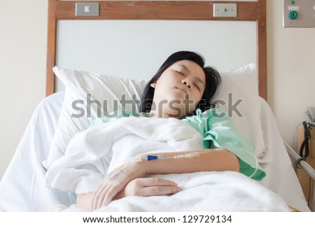 Woman lying on a bed while closing her eyes in hospital
