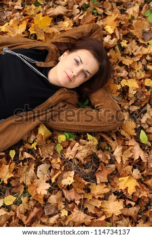 woman lying on a carpet of leaves in autumn park