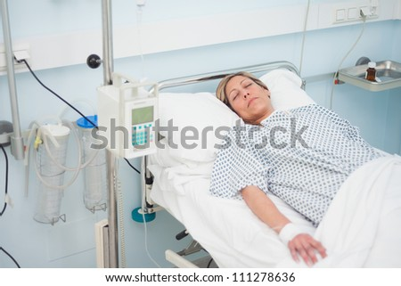 Woman lying on a medical bed with closed eyes in hospital ward