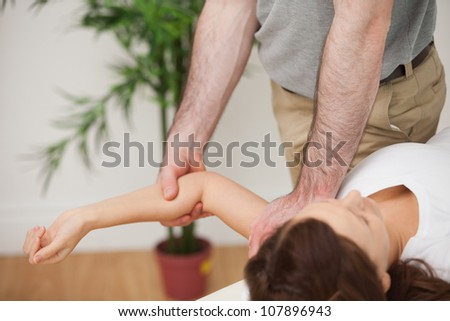 Woman lying on a medical table while being manipulated in a room
