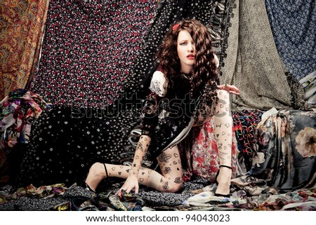 Woman lying on a pieces of colorful fabrics