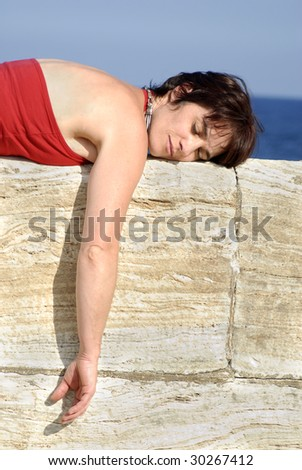 woman lying on a stone wall