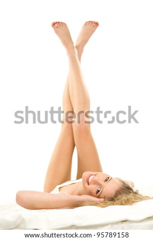 Woman lying on bed with legs raised